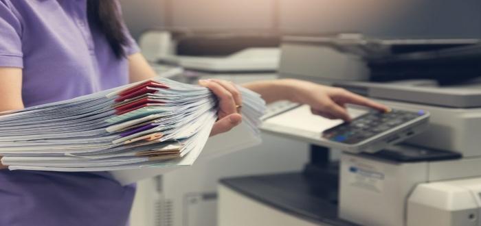 Mujer con fotocopias en un negocio de imprenta