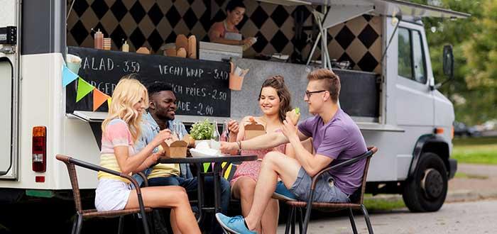 personas-comiendo-sentadas-en-una-mesa-junto-a-un-food-truck