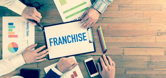 """manos y objetos de oficina sobre un escritorio alrededor de una planilla con la leyenda """"franchise"""""""