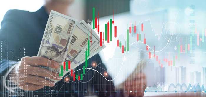 persona sosteniendo dinero tras gráficas de inversión en primer plano