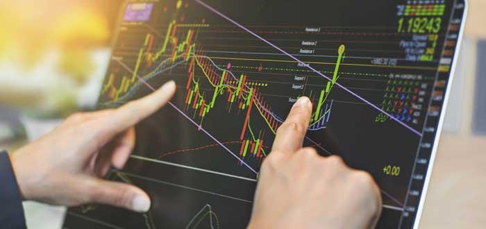 dos manos señalando en pantalla gráficas del mercado de divisas
