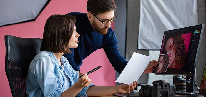 hombre y mujer revisando fotografía en una agencia gráfica, uno de los negocios rentables en Colombia