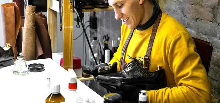 hombre arreglando zapatos como uno de los negocios rentables en Colombia