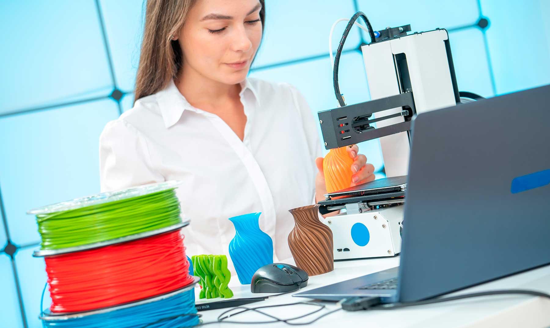 mujer imprimiendo jarrones en impresora 3d