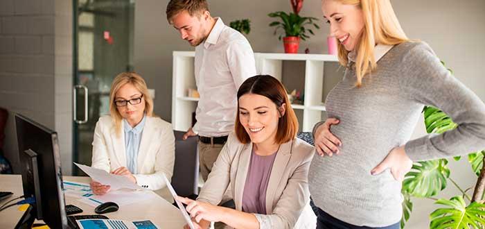 mujer embarazada con grupo de trabajo frente a un computador
