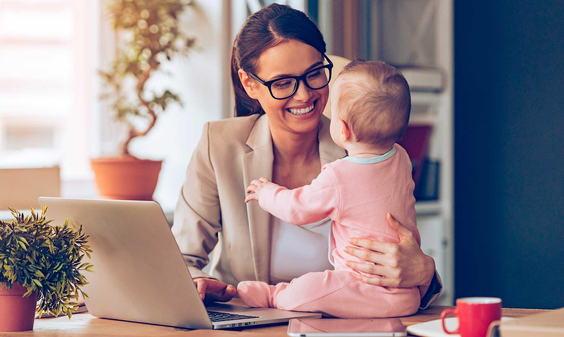 mujer con su bebé sentada frente al computador