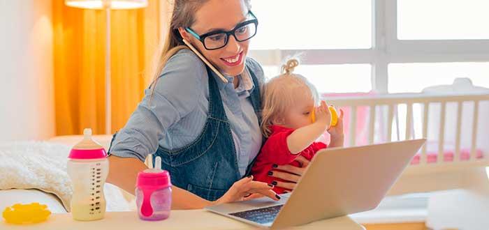 mujer sosteniendo a su bebé mientras trabaja frente a computador (negocios desde casa para madres solteras)