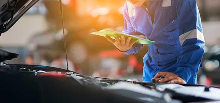mecánico con tabla en la mano analizando un auto en un taller de alineación y balanceo