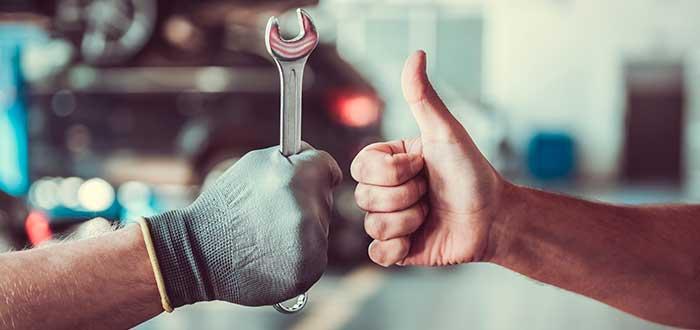 mano de mecánico sosteniendo una llave y mano de otra persona con el pulgar arriba