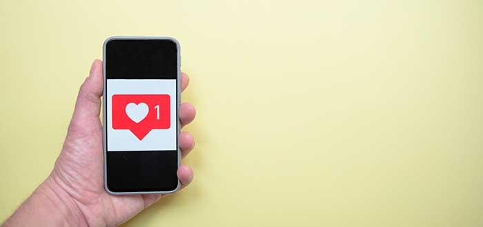 mano sosteniendo un teléfono con imagen del ícono de me gusta de instagram