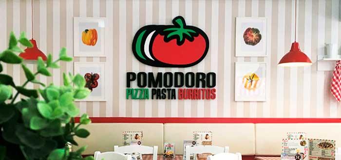 Fotografía de un local de la franquicia Pomodoro adentro, con el logo de la franquicia en una pared
