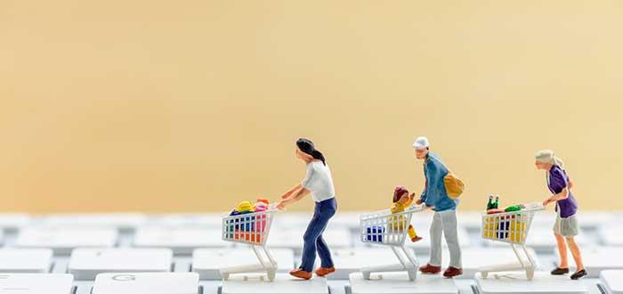 muñequitos en miniatura con carritos de mercado sobre un teclado (simbólico para franquicias online)