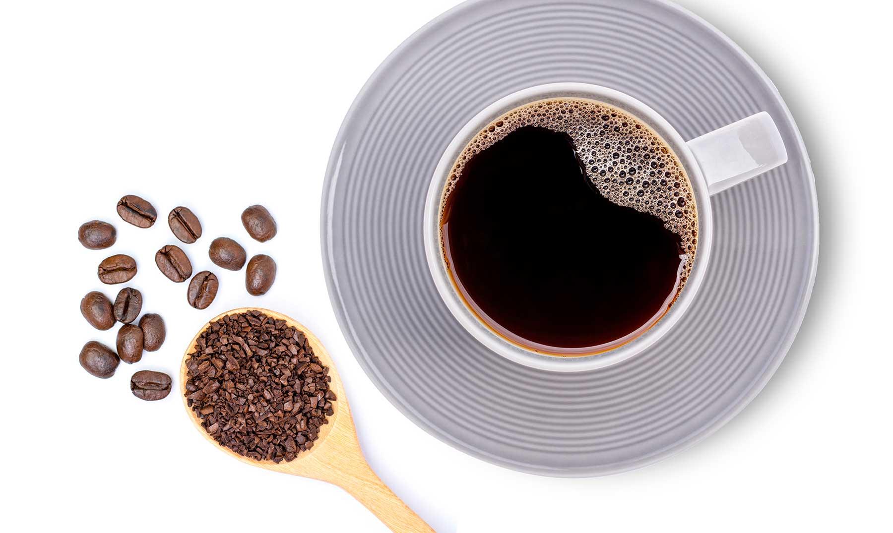 taza de café con cuchara llena de granos de café