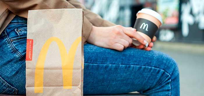 persona sentada con un mccafe y una bolsa de una franquicia McDonald's