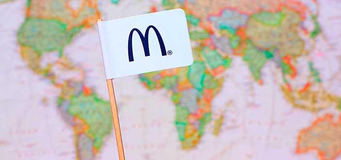 Bandera con el logo de McDonald's sobre un mapamundi