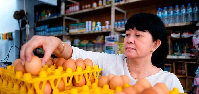 mujer colocando huevos en una cubeta en tienda de barrio