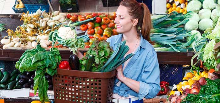 mujer con canasta llena de verduras en verdulería