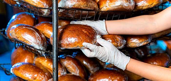 manos con guantes tomando un pan en tienda de barrio
