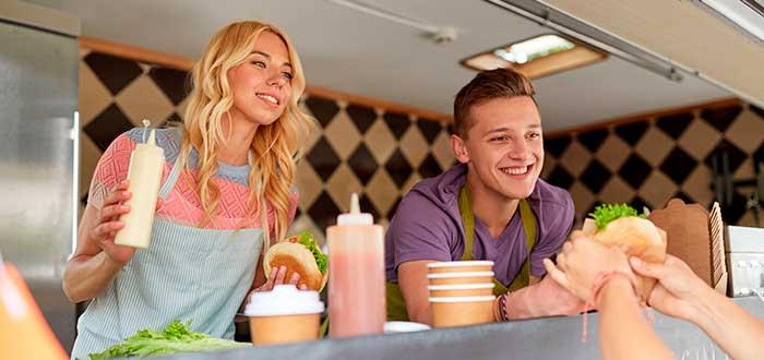 dos jóvenes vendiendo hamburguesas en un camión de comidas