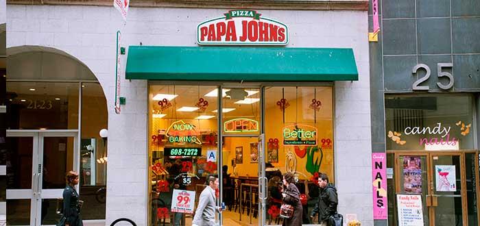 transeuntes pasando frente a un Papa John's