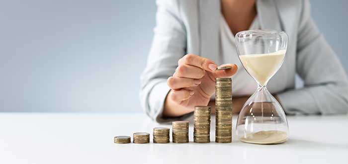 persona apilando monedas en escalera sobre una mesa junto a reloj de arena