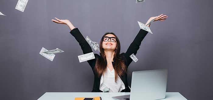 mujer arrojando billetes hacia arriba mientras está sentada en un escritorio con computador