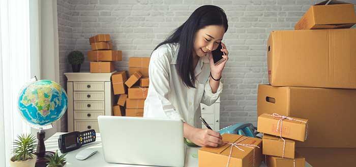 mujer marcando cajas para enviar por negocio por internet