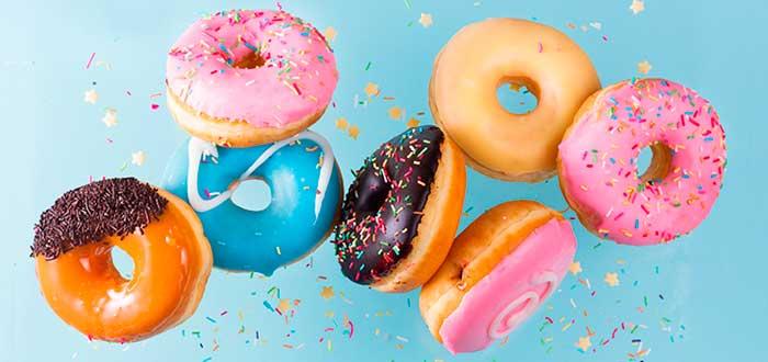 siete donas de diferentes colores en un fondo azul cayendo
