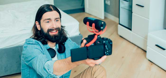Un hombre barbudo y expresivo sostiene una cámara con micrófono para ganar dinero en Youtube