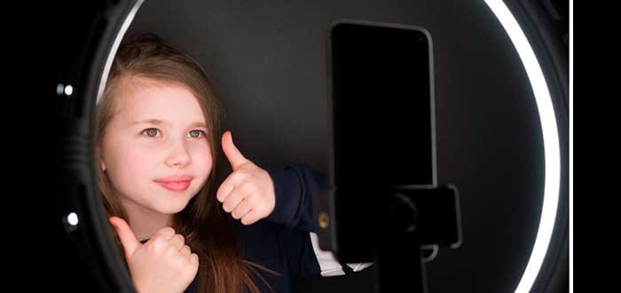 niña frente a un smatphone probando un anillo de luz mientras hace un gesto de pulgares arriba