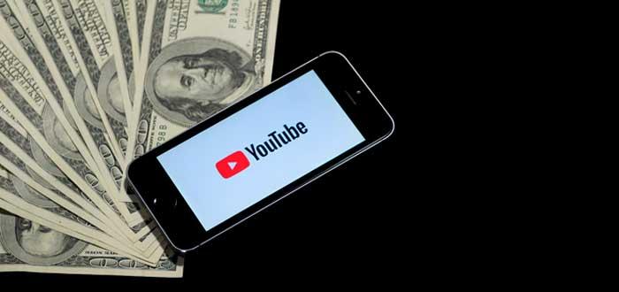 teléfono con la aplicación de Youtube abriendo sobre un montón de billetes que simbolizan que es posible ganar dinero en Youtube